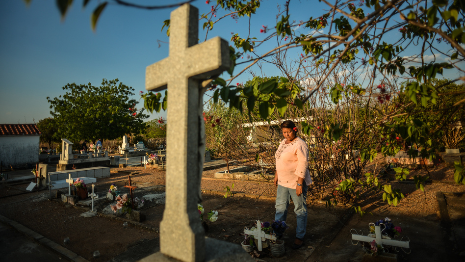 Eloisa Barrios visits the humble graves of nine male family members in the Guanayen cemetery. She says all nine were killed by the police, in what was a vendetta against her family. Recently, a 10th member of the family was stabbed to death. He was 17. (Meridith Kohut for NPR)