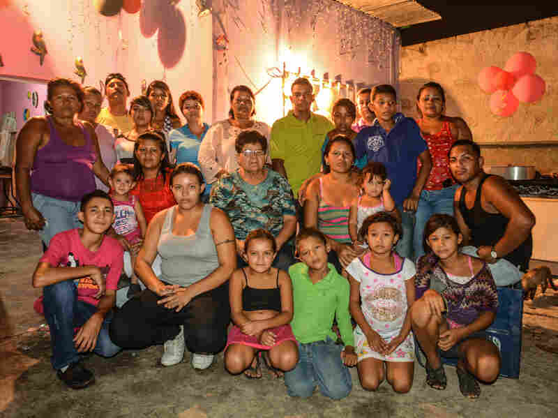 """Members of the Barrios family pose for a family portrait during a birthday party at a family home in Cagua, Venezuela. Nine men in the Barrios family have been allegedly murdered by the police. The party was largely attended by female family members — when asked why, several women said in unison, """"because there aren't any men left."""""""