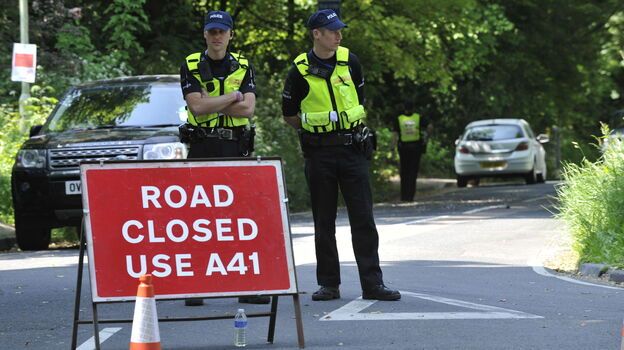 """What goes on up the road is only for those in the know to know: Police stood guard Thursday near the Grove Hotel in Watford, England, where """"The Bilderberg"""" group is meeting this year. (PA Photos /Landov)"""