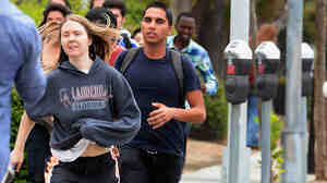 Students rush to safety after shots were fired near the Santa Monica College Friday. According to reports, at least six people were shot, and a suspect was taken into custody. One shooting victim died of her injuries during surgery.