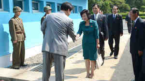 South Korea's delegate (left) shakes hands with North Korea's head of working-level delegation Kim Song-Hye as she crosses the military demarcation line for the meeting at border village of Panmunjom.