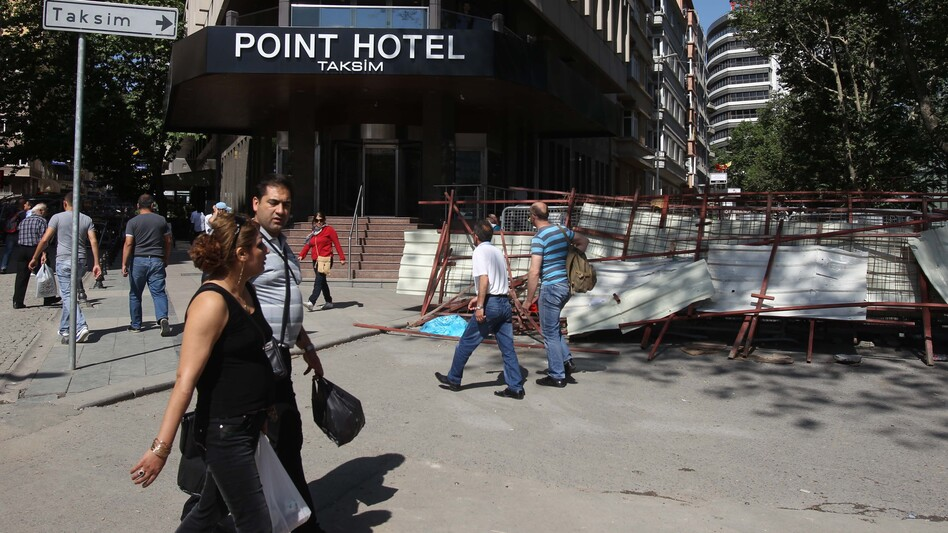 Pedestrians pass a barricade outside a hotel at Taksim Square, Istanbul. Business people say they are nervous that protests are cutting deep into tourism. (AP)