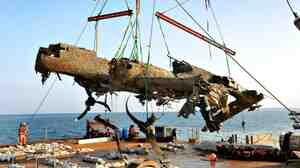 A Dornier 17 bomber, which Germany used in the first years of World War II, is lowered onto a salvage barge in the English Channel, 70 years after the craft was shot down.