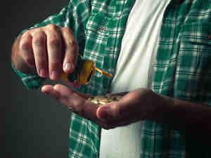 Man shaking pills into his hand.