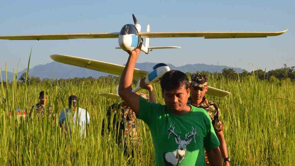 Park rangers and army personnel in Nepal carry unmanned aerial vehicles used to track wildlife and poaching activity. The drones, which can be programmed to fly automatically, are outfitted with ca