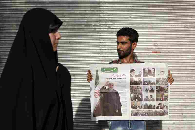 A supporter of presidential candidate Hassan Rowhani, a former nuclear negotiator for Iran, holds a newspaper with Rowhani's pictures during a rally in Tehran, on June 9.
