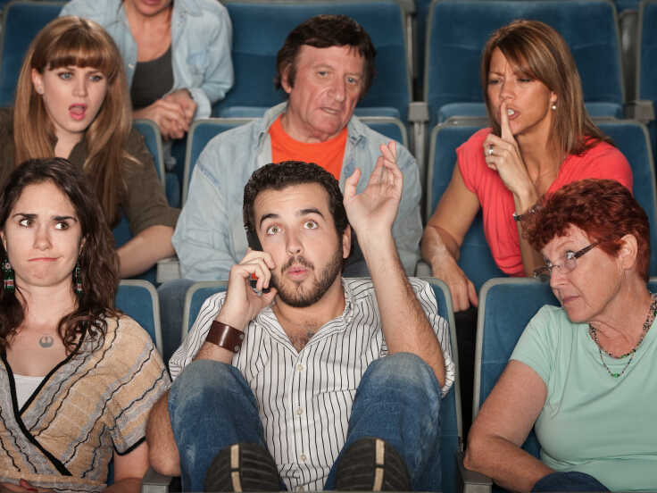 Man on the phone in a theater.