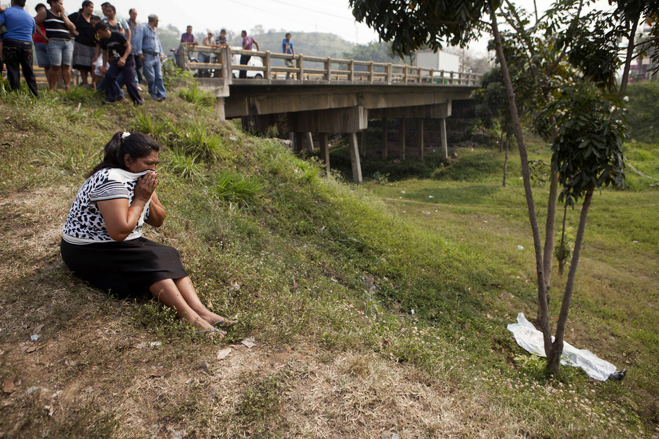 A woman cries near the body of the Justiniano Lara, 51, after he was killed by unidentified assailants in San Pedro Sula, Honduras, on March 25. With 91 murders per 100,000 people, the small Central American nation is the most violent in the world, and San Pedro Sula the most violent city. (AP)