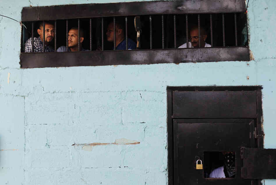 Members of the Calle 18 street gang look out from their cell at the prison in San Pedro Sula. The prison houses the country's most violent criminals.