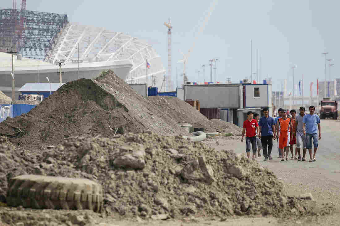 As Sochi, Russia, prepares to host the 2014 Olympic Games, workers walk past piles of dirt at the construction site of Fisht Stadium and Olympic Park on May 20.