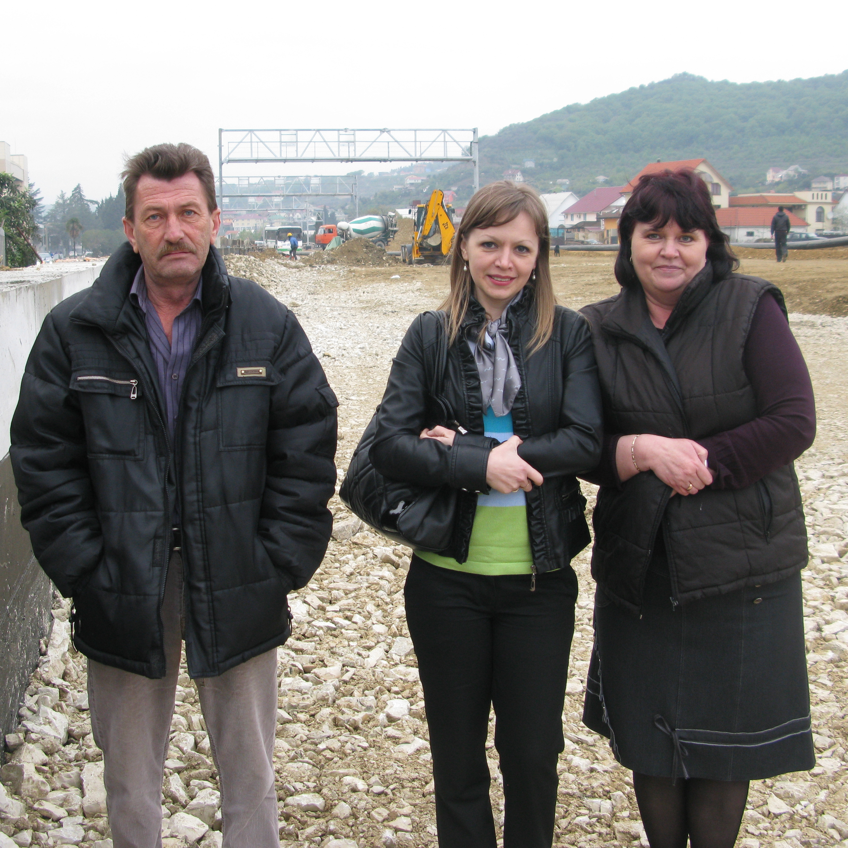 Yulia Saltykova (center) stands with her family on the site of a highway that, when finished, will cut off all access to their home. The family is one of many that say they have been displaced or harmed by Sochi's Olympic construction.