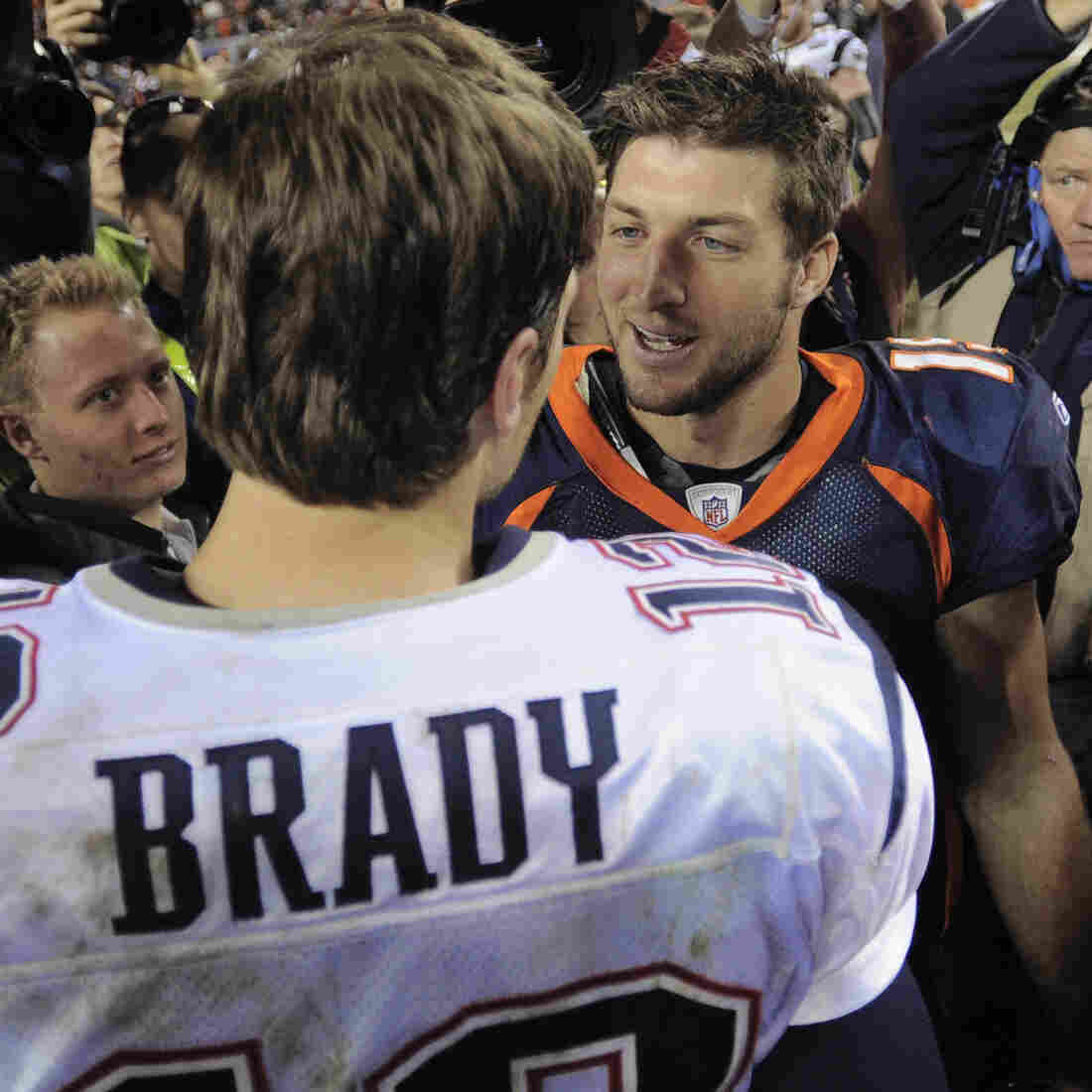 Tim Tebow (right) shakes hands with New England Patriots quarterback Tom Brady after the Patriots defeated the Broncos on Dec. 18, 2011. Now, they're due to be teammates.
