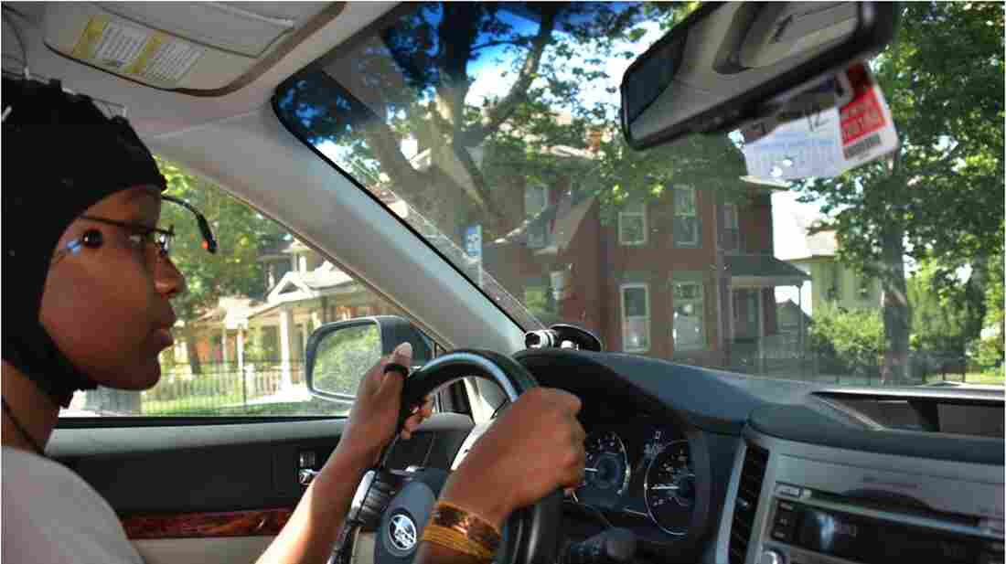 A University of Utah volunteer drives through Salt Lake City's Avenues neighborhood as a camera tracks her eye and head movement. Another device records driver reaction time, and a cap fitted with sensors charts brain activity.