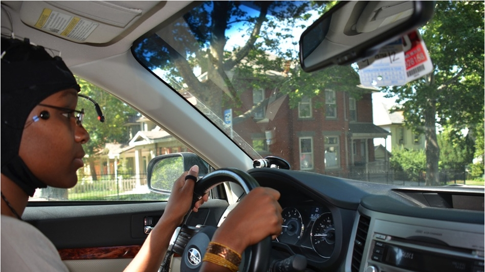 A University of Utah volunteer drives through Salt Lake City's Avenues neighborhood as a camera tracks her eye and head movement. Another device records driver reaction time, and a cap fitted with sensors charts brain activity. (AAA Foundation for Traffic Safety)