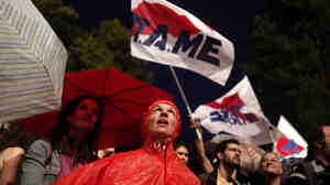 Protesters wave flags outside the Athens headquarters of broadcaster ERT on Wednesday. Prime Minister Antonis Samaras shut down the network Tuesday, but workers are occupying the building.