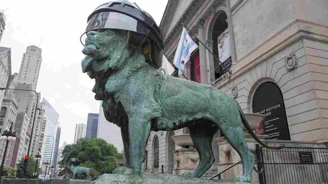An oversized Chicago Blackhawks hockey helmet sits on one of the lion sculptures outside the entrance to the Art Institute of Chicago in celebration of the team's upcoming appearance in the Stanley Cup Final in Chicago. The Blackhawks host the Boston Bruins in Game 1 on Wednesday.