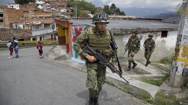 Colombian army soldiers patrol Medellin's Loma de Cristobal neighborhood after warring gangs forced dozens of families to flee. Medellin used to be the most dangerous city in the world, but officials embarked on innovative projects designed to make life better in tough neighborhoods. (Paul Smith for NPR)