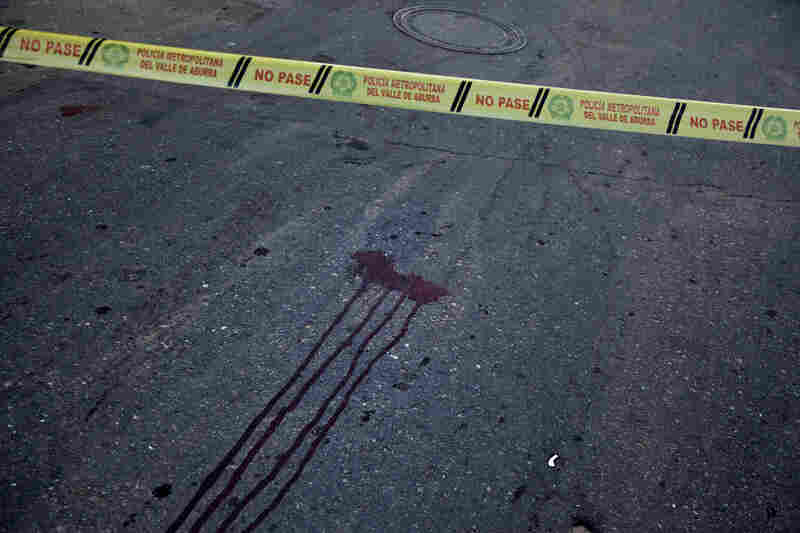 A double homicide in the neighborhood known as Beln in Medellin's southwest is marked by bloodstains. While the homicide rate has dropped by 80 percent, Medellin is not crime-free.
