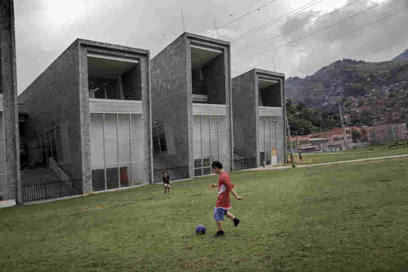 Boys play soccer in front of one of the new schools built by the city to improve the troubled Comuna 13 district.