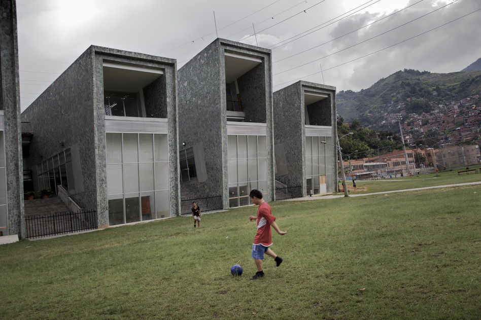 Boys play soccer in front of one of the new schools built by the city to improve the troubled Comuna 13 district. (Paul Smith for NPR)