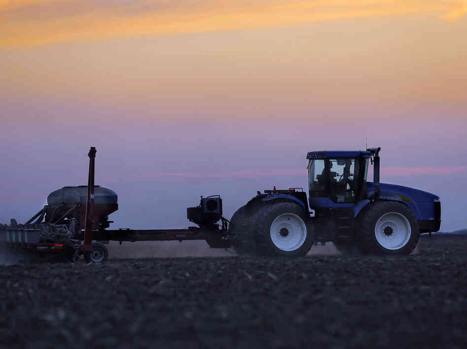 A central Illinois farmer plants corn seed into the evening in Farmingdale, Ill.