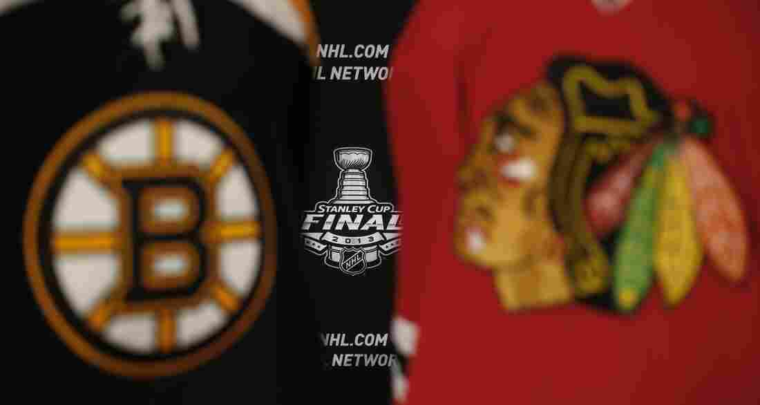 The 2013 NHL Stanley Cup logo is seen between the sweaters of the Boston Bruins and Chicago Blackhawks. The Game 1 puck drops at 8 p.m. Wednesday in Chicago.