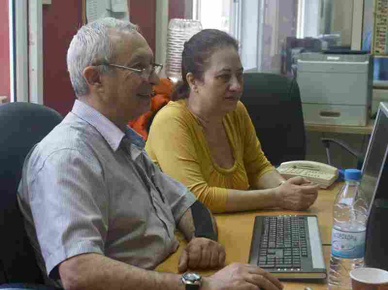 ERT foreign editors Tassos Ioannides (left) and Glykeria Kyriakidou, who lost their jobs as part of the shutdown, scan the news wires. European public broadcasters such as Tele Bruxelles in Belgium are airing ERT programming to protest the shutdown.