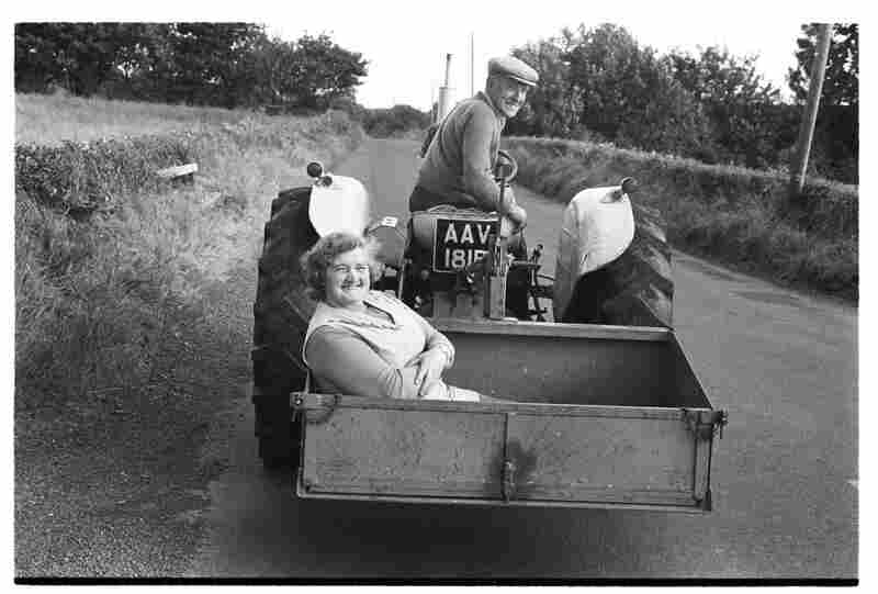 A farmer takes his wife shopping on the tractor bucket, 1980s.
