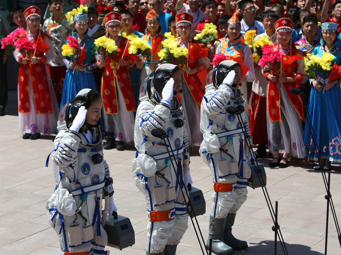 Chinese astronauts (from left) Wang Yaping, mission commander Nie Haisheng and Zhang Xiaoguang gesture as they prepare to board the Shenzhou-10 spacecraft in Jiuquan, China, on Tuesday.