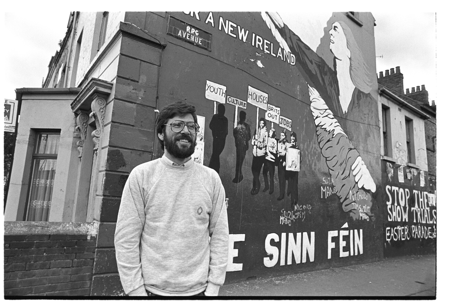 Gerry Adams, president of Sinn Fein, posing in front of a Sinn Fein republican wall mural in Belfast, Northern Ireland, mid-1980s.