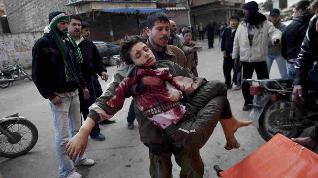 A man carries a boy badly wounded by the fighting between government forces and rebels on March 11, 2012. The U.N. says at least 93,000 people have been killed in the fighting.