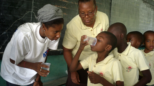 Boys at the L'Ecole Les Freres Clement elementary school in Jacmel, Haiti, line up to take deworming pills that protect against elephantiasis.