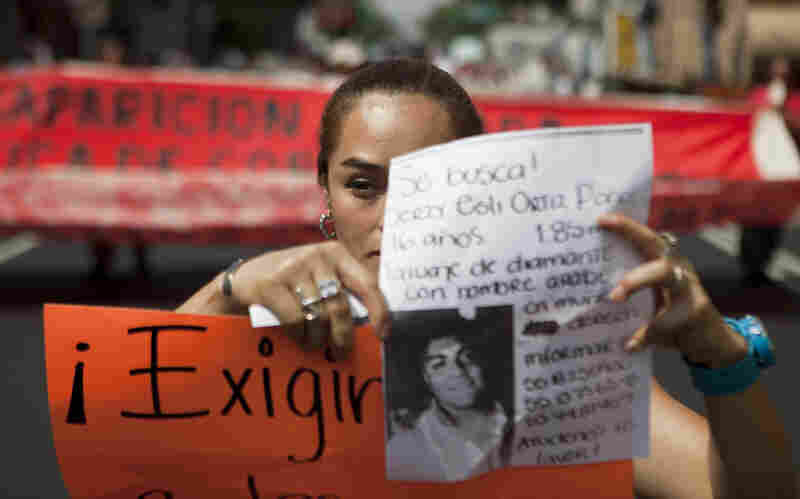 A woman holds up a sign with details of her recently disappeared relative during a protest in Mexico City, on May 30.