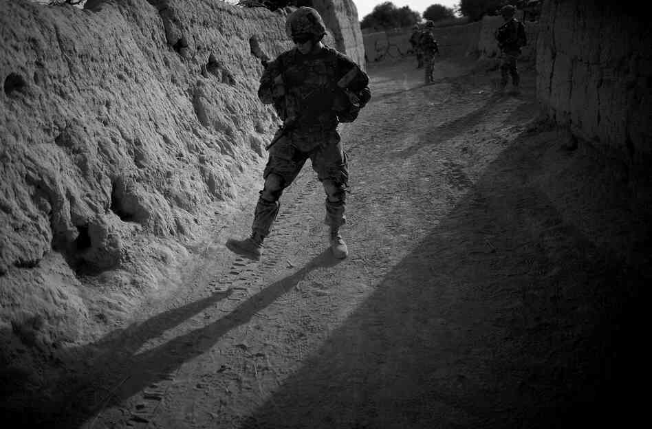 A soldier is careful to follow the line that has been checked for roadside bombs while on a foot patrol in Panjwai. IEDs are a major problem in the area, particularly in areas where Americans have handed responsibility over to Afghan security forces.
