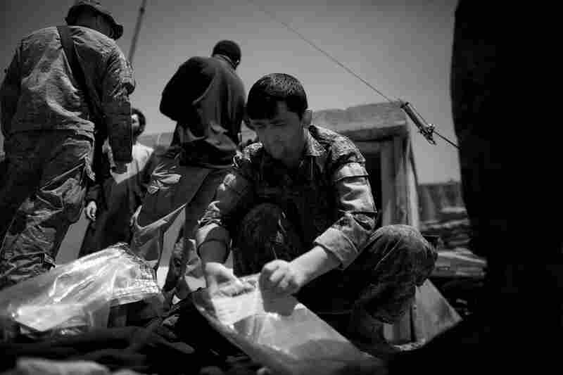 An Afghan National Army soldier loads evidence into a plastic bag. The materials, including what appeared to be triggers and IED plans, were found in the vests of two men arrested as Taliban bomb-makers.