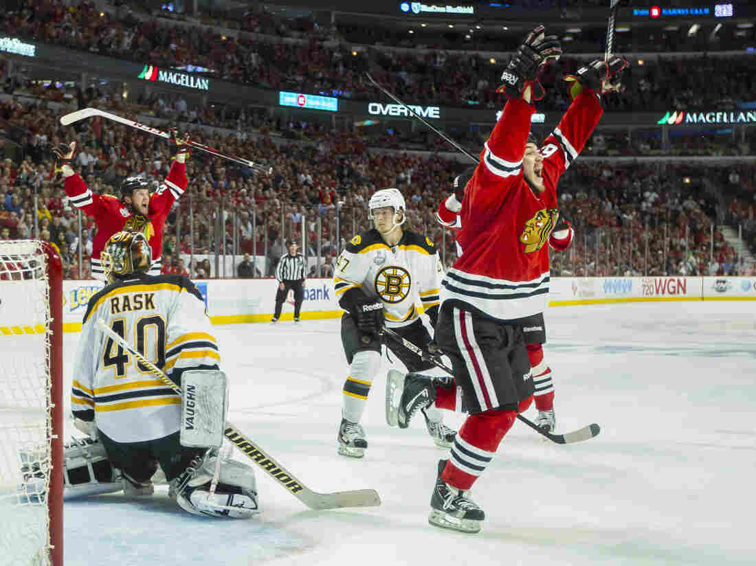 The thrill of victory; the agony of defeat: Andrew Shaw of the Chicago Blackhawks (right) celebrates after the game-winning goal goes in. Boston Bruins goaltender Tuukka Rask  looks back toward the puck that's now in his net.