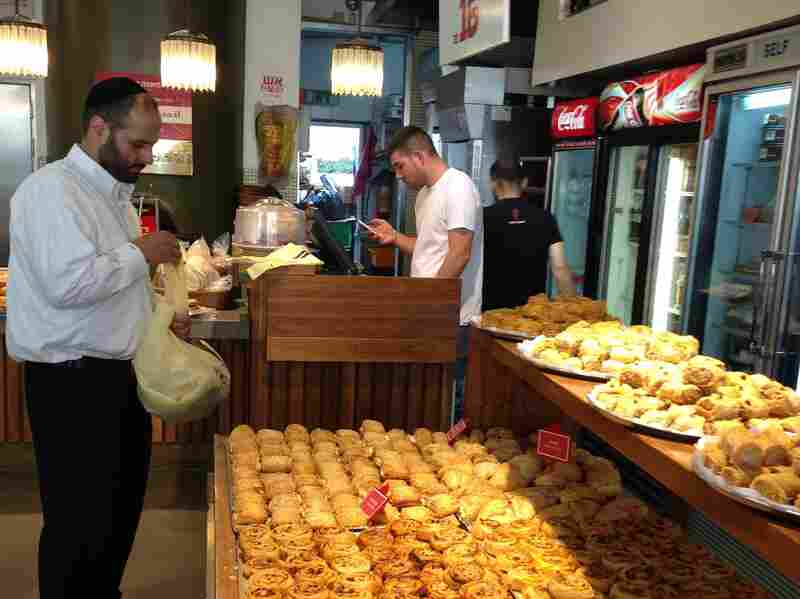 A man loads up on pastries at a Jerusalem shop. The shop owner says the new kosher rules are well-intentioned but will never fly.