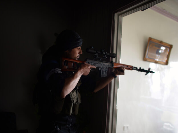 A Syrian rebel aims his sniper rifle at Syrian government forces in the Sheikh Maqsud district of Aleppo, in April.