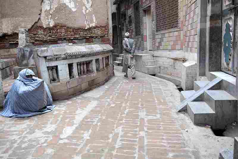 A woman sits on a street corner in the old city of Peshawar, waiting for a passerby's attention. She does not have any other source of income and is forced to beg.
