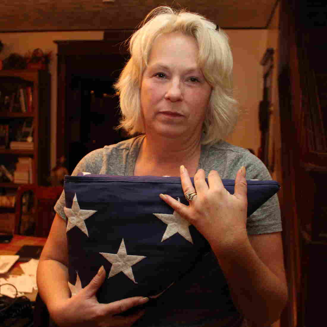 Anna holds the flag that was draped over Nick's coffin at his memorial service. She and her husband, Michael, have created a shrine to Nick in their dining room.