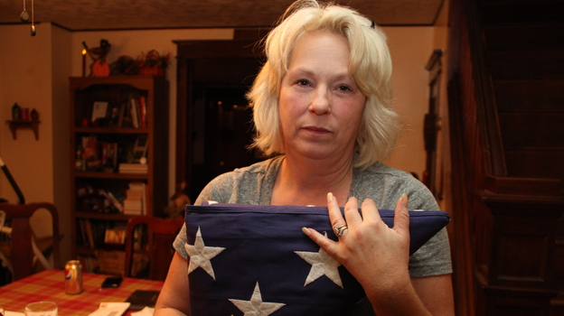 Anna holds the flag that was draped over Nick's coffin at his memorial service. She and her husband, Michael, have created a shrine to Nick in their dining room. (Courtesy of Long Haul Productions)