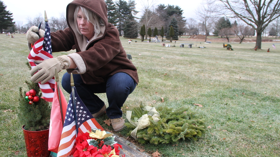 Anna Rodriguez tends the grave of her son, Nick. She learned shortly after Nick's death that, because his death was a suicide, his name would not be included on a local memorial to fallen soldiers. She has since found a memorial garden in York, Pa., that will add Nick's name to its memorial wall this summer. (Courtesy of Long Haul Productions)