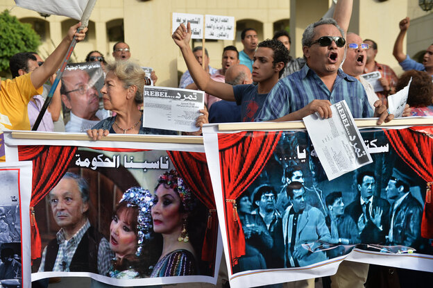 Egyptian employees of the Cairo Opera House and opponents of Egypt's Islamist President Mohamed Morsi hold placards during a demonstration inside the opera's compound in Cairo on May 30, following the dismissal of the head of the opera house. The firing is the latest salvo in a cultural war between artists and the ruling Muslim Brotherhood.