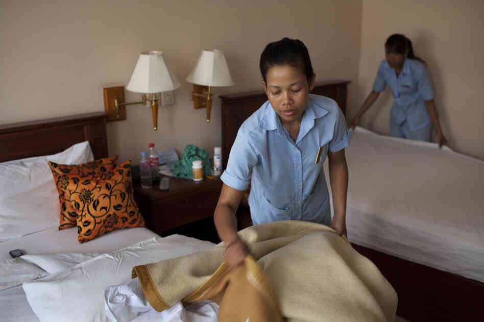 Srey Tol (left) and another employee clean a room at the hotel.