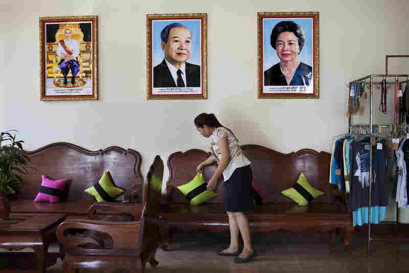 Photographs of Cambodia's royal family, including King Norodom Sihamoni (left), the late King Father Norodom Sihanouk (center) and Queen Mother Norodom Monineath, hang on the wall in the hotel's lobby.