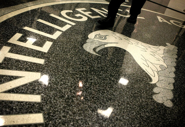 A man walks across the seal of the Central Intelligence Agency at the CIA headquarters.