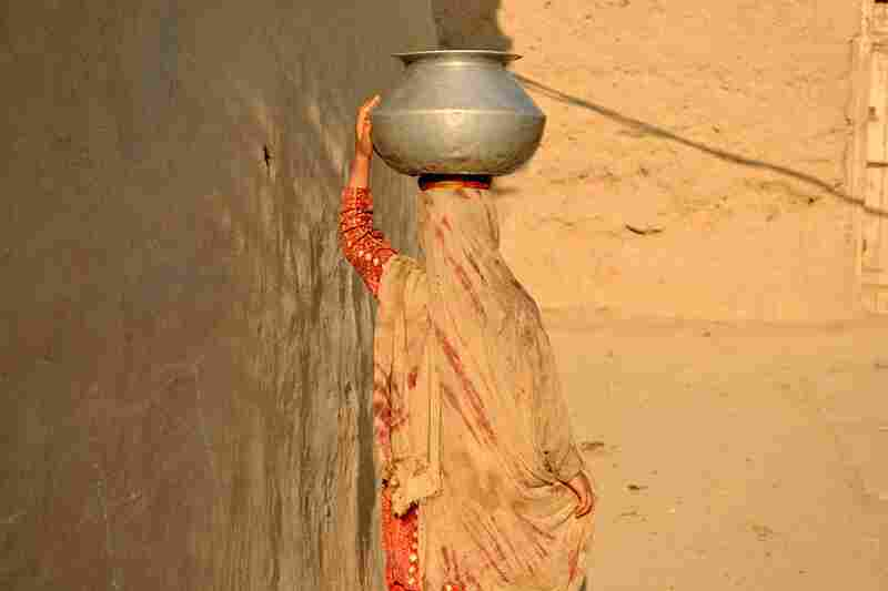 A woman returns home after fetching water in a village in Mohmand Agency.