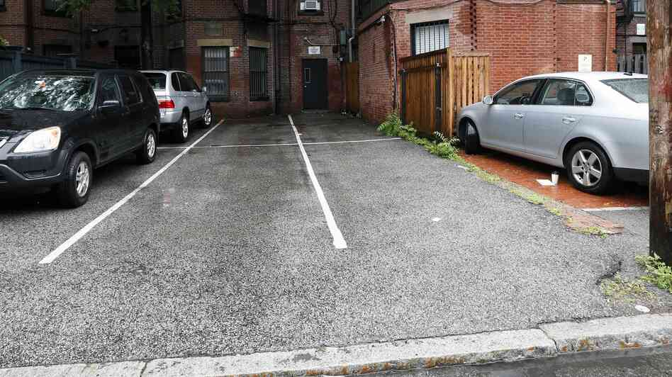 Parking spaces behind 298 Commonwealth Avenue in Boston are seen Friday. The two open spaces at right, front and back, were sold at auction for $560,0