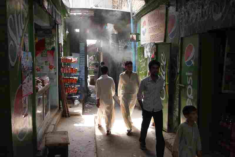 Men pass through a busy market of Saidpur village in Islamabad, where the locals buy their daily produce.