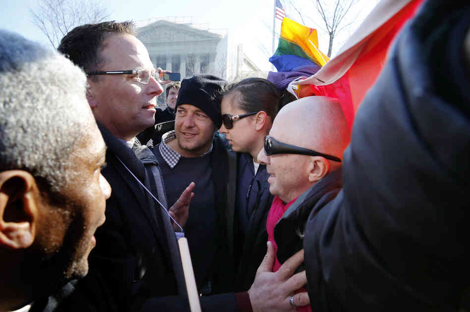 Anti-gay marriage protesters (left) try to persuade same-sex marriage supporters to get out of the way of their march in front of the Supreme Court.